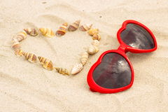 Heart of shells and sunglasses on sand at the beach Royalty Free Stock Photos