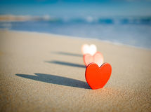 Heart on the shore. A landscape crop of a cut out red hearts with their shadow on the seashore Stock Photography
