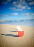 Heart on the shore. A portrait crop of cut out red hearts with their shadows on the seashore Royalty Free Stock Image
