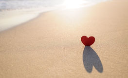 Heart on the shore 3. A landscape crop of a cut out red heart with shadow on the seashore Stock Photo