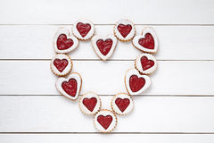 Heart of the shortbread heart-shaped cookies with jam on white wooden table background. Stock Photos