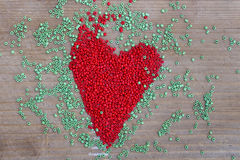 Heart. Sign made of red and green beads on a wooden surface Royalty Free Stock Photo