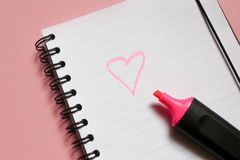 Heart sign on notepad and pink marker on pink background, a love note using a pink marker. Valentine& x27;s day stock photo