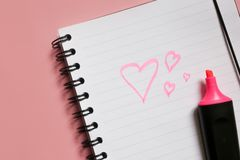 heart sign on notepad and pink marker on pink background, a love note using a pink marker stock image