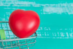 Heart sign in shopping cart on color wood. Red heart sign in shopping cart on color wood Stock Image