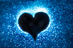 Heart silohuette on a blue bokeh background Royalty Free Stock Photography