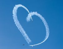 A heart in the sky. Two biplanes skywriting a heart Royalty Free Stock Photos