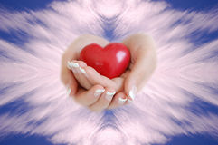 Heart in the Sky. Hands holding a red heart in the sky Royalty Free Stock Photos