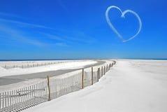 Heart in sky over beach. Sky writing heart over white sand on coastal island Royalty Free Stock Image