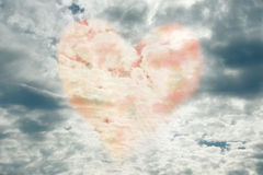 Heart in the sky. Sky with a warm heart making its appearance through dark stormy clouds; symbol of love and hope for tomorrow Royalty Free Stock Photos