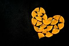 Heart from slices of orange on a black background royalty free stock photo