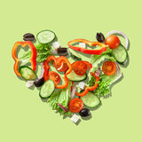 Heart from slices of vegetables. Isolated on a green background Royalty Free Stock Photo