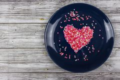 Heart from small multi-colored candies. On a blue plate. Valentine`s Day. Valentine card. With copy space stock photos