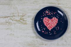 Heart from small multi-colored candies. On a blue plate. Valentine`s Day. Valentine card. With copy space stock photo