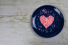 Heart from small multi-colored candies. On a blue plate. Valentine`s Day. Valentine card. With copy space royalty free stock image
