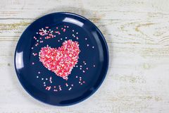 Heart from small multi-colored candies. On a blue plate. Valentine`s Day. Valentine card. With copy space royalty free stock images