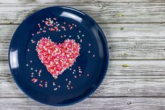 Heart from small multi-colored candies. On a blue plate. Valentine`s Day. Valentine card. With copy space stock images