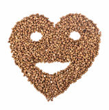 Heart with smiling face from buckwheat. On white isolated background Royalty Free Stock Photography