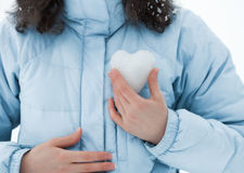 Heart of Snow. Young woman holding a snow heart at her chest royalty free stock photos