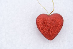 Heart on snow. Christmas tree ornament rests upon snow Stock Images