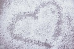 Heart in snow on grey background Stock Photos