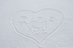 Heart on the snow. The inscription on the snow, I love you inside the heart Stock Photos
