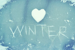 Heart from snow and the word WINTER scratched on ice. Winter theme. Royalty Free Stock Images