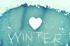 Heart from snow and the word WINTER scratched on ice. Winter theme. Royalty Free Stock Image