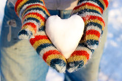 The heart of the snow in your hand, palm in multicolored mittens Royalty Free Stock Image