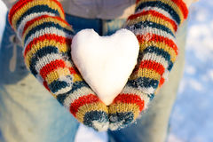 The heart of the snow in your hand, palm in multicolored mittens Royalty Free Stock Images