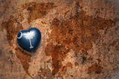 Heart with south carolina state flag  on a vintage world map crack paper background. Concept Royalty Free Stock Photography