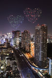 Heart sparkle Fireworks celebrating over Tokyo cityscape at nigh Stock Image