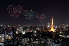 Heart sparkle Fireworks celebrating over Tokyo cityscape at nigh Stock Photos