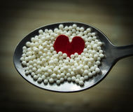 Heart in spoon with white balls. Royalty Free Stock Photography