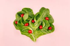 Heart of spring healthy food - cherry tomatoes and leaves spinach on pink background. Valentine`s day backdrop. stock photo