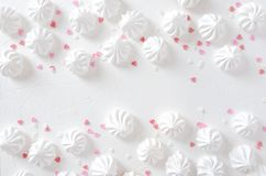 Rows of white tasty meringues and decoration.Empty space in the middle for your design royalty free stock image
