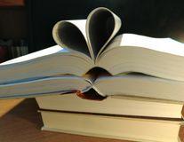 Hearts on books on a black background stock images
