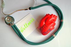 Heart with stetoscop. Dreen modern stethoscope with red heart on white table Royalty Free Stock Photography