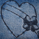 Heart stitched on denim. A heart with a bow stitched on denim or jeans Stock Photo