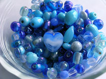 Heart of Stone. One stone heart sits in the center of a bowl full of round glass beads royalty free stock images
