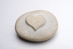 Heart of stone. A stone with an engraved heart sitting on a metal surface Royalty Free Stock Photography