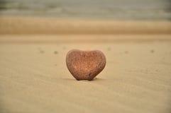 Heart stone on the beach. Heart shaped stone on a sandy beach Stock Photos