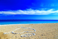 Heart of stone, and the first letters of the names laid out on the shore of pebble beach Royalty Free Stock Image