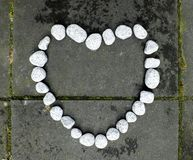 Heart of stone made of small white stones on the dark stone background royalty free stock image