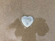 Heart stone on shadow and sand beach. royalty free stock photo