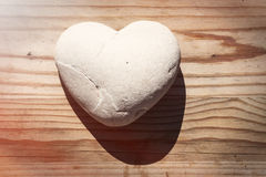 Heart stone with shadow on wooden table. A stone has the shape of a heart and creates a romantic shadow. The stone stands on a wooden table with a knot on the Stock Photography