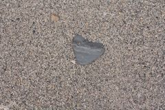 Perfect heart shape natural stone. Heart shaped natural pebble laying on the beach stock image