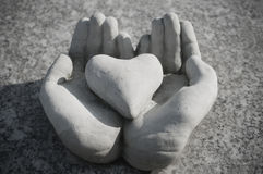 Heart in stoned hands on a tomb. Heart in stoned hands in cemetery on a tomb Stock Photography