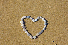Heart from stones. The heart is lined with stones on the sand Stock Image