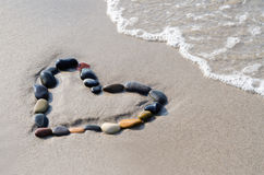 Heart of stones. A heart of stones in the surge on the beach Royalty Free Stock Photo